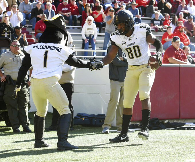 Vanderbilt tight end Jared Pinkney celebrates with Mr. Commodore after a touchdown catch against Arkansas in the first half of an NCAA college football game Saturday, Oct. 27, 2018, in Fayetteville, Ark. (AP Photo/Michael Woods)