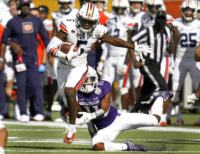 Auburn wide receiver Kobe Hudson, left, makes a move to get past Northwestern defensive back A.J. Hampton, right, during the first half of the Citrus Bowl NCAA college football game, Friday, Jan. 1, 2021, in Orlando, Fla. (AP Photo/John Raoux)