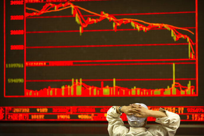 A Chinese investor monitors stock prices at a brokerage house in Beijing, Friday, June 22, 2018. Asian stocks fell Friday following Wall Street losses overnight as investors were still wary over trade disputes between China and the U.S. as well as between the U.S. and Europe that could hurt corporate profit and jobs. (AP Photo/Mark Schiefelbein)