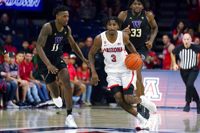Arizona guard Dylan Smith (3) drives past Washington guard Nahziah Carter (11) during the second half of an NCAA college basketball game Saturday, March 7, 2020, in Tucson, Ariz. Washington won 69-63. (AP Photo/Rick Scuteri)