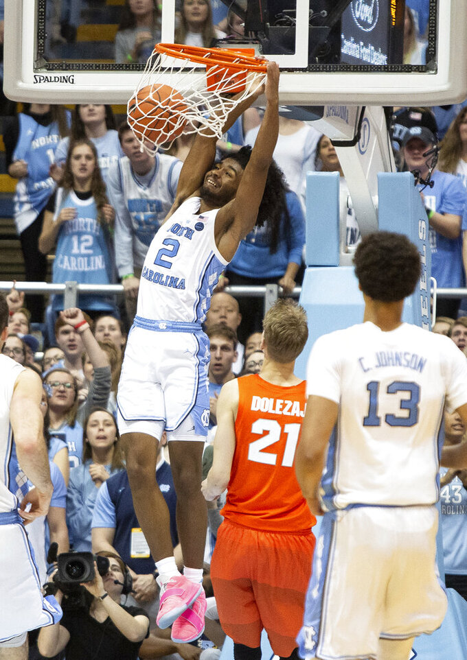 North Carolina's Coby White (2) dunks the ball ahead of Syracuse's Marek Dolezaj (21) during the second half of an NCAA college basketball game in Chapel Hill, N.C., Tuesday, Feb. 26, 2019.  White had a season-high 34 points as No. 5 North Carolina defeated Syracuse 93-85. (AP Photo/Ben McKeown)