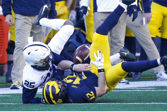 Michigan quarterback Cade McNamara is tackled by Penn State cornerback Daequan Hardy (25) during the second half of an NCAA college football game against Penn State, Saturday, Nov. 28, 2020, in Ann Arbor, Mich. (AP Photo/Carlos Osorio)