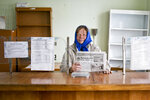 In this Oct. 12, 2019, photo, Tetiana Petrovych, a postmistress in Nebelytsia village, Ukraine, poses for a photo during an interview with The Associated Press. Most of Ukraine's rich farmland is carved up into small plots owned by about 7 million people, like Petrovych. They are forbidden by law from selling it, although Ukraine's new president wants to change that. (AP Photo/Andrew Mosienko)