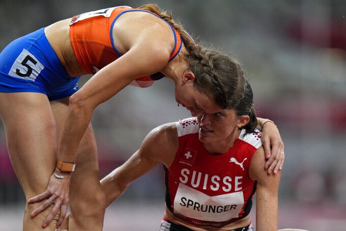 Femke Bol, left, of the Netherlands, embraces Lea Sprunger, of Switzerland, after their semifinal of the women's 400-meter hurdles at the 2020 Summer Olympics, Monday, Aug. 2, 2021, in Tokyo. (AP Photo/Petr David Josek)