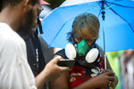 Johnnie Mae Holmes-Wilson wears a gas mask while listening to the live feed outside the Glynn County Courthouse while a preliminary hearing is being held inside for for Travis McMichael, Gregory McMichael and William Bryan, Thursday, June 4, 2020, in Brunswick, Ga. The three are accused of shooting of Ahmaud Arbery while he ran through their neighborhood in February. (AP Photo/Stephen B. Morton)