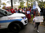 Dozens of Chicago Teachers Union members, CPS students and supporters march around a police car blocking the street and continue to march through the streets of Chicago's Hyde Park neighborhood during the