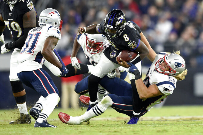 Baltimore Ravens quarterback Lamar Jackson (8) is brought down by New England Patriots defensive end Chase Winovich (50) and defensive tackle Adam Butler (70) during the second half of an NFL football game, Sunday, Nov. 3, 2019, in Baltimore. Patriots' Jonathan Jones looks on during the play. (AP Photo/Gail Burton)