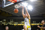 Iowa center Luka Garza (55) dunks as Kennesaw State forwards Drew Romich, left, and Bryson Lockley, right, defend during an NCAA college college basketball game, Sunday, Dec. 29, 2019, in Iowa City, Iowa. (Joseph Cress/Iowa City Press-Citizen via AP)