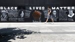 "FILE - In this June 6, 2020, file photo, a man walks past a ""Black Lives Matter"" mural painted on the boarded-up Apple Store, in Boston. Black Lives Matter has gone mainstream — and black activists are carefully assessing how they should respond. (AP Photo/Michael Dwyer, File)"