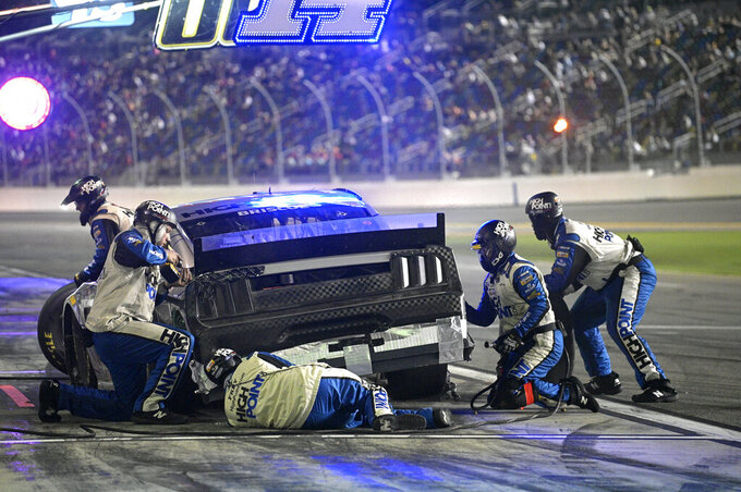 Crew members work on Chase Briscoe's car during a pit stop in a NASCAR Cup Series auto race at Daytona International Speedway, Saturday, Aug. 28, 2021, in Daytona Beach, Fla. (AP Photo/Phelan M. Ebenhack)