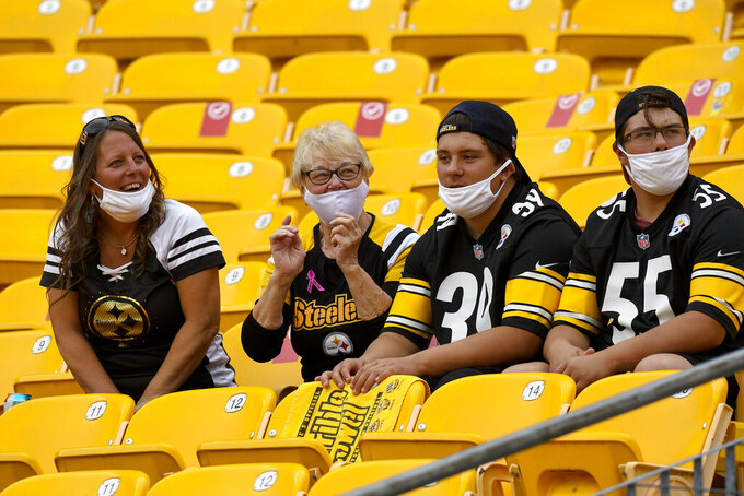 Steelers fans watch warm ups before an NFL football game between the Pittsburgh Steelers and the Philadelphia Eagles in Pittsburgh, Sunday, Oct. 11, 2020. It is the first Steelers football game this season that some 5000 fans will be allowed to attend. (AP Photo/Don Wright)