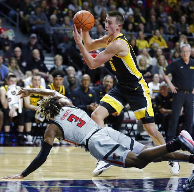 Iowa's Joe Wieskamp (10) grabs the ball away from Texas Tech's Jahmi'us Ramsey (3) during the first half of an NCAA college basketball game Thursday, Nov. 28, 2019, in Las Vegas. (AP Photo/John Locher)