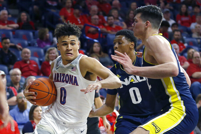 Arizona guard Josh Green (0) drives past Northern Arizona's Cameron Satterwhite (0) and Brooks DeBisschop during the second half of an NCAA college basketball game Wednesday, Nov. 6, 2019, in Tucson, Ariz. (AP Photo/Rick Scuteri)