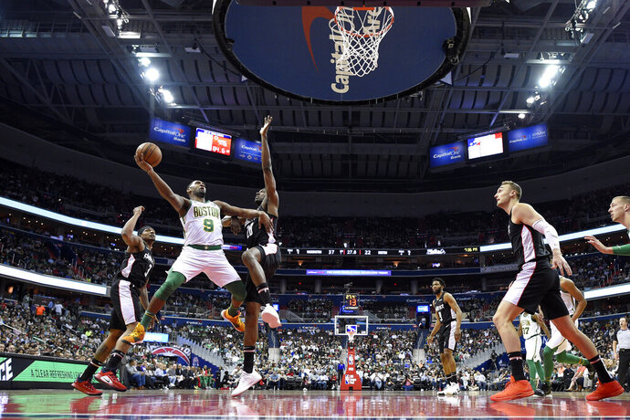 Boston Celtics guard Brad Wanamaker (9) shoots as Washington Wizards guard Bradley Beal, left, and center Ian Mahinmi (28) defend during the first half of an NBA basketball game Tuesday, April 9, 2019, in Washington. The Celtics won 116-110. (AP Photo/Nick Wass)