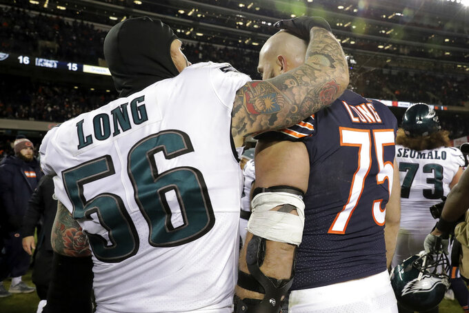 Philadelphia Eagles defensive end Chris Long (56) and his brother, Chicago Bears offensive guard Kyle Long (75) greet each other after an NFL wild-card playoff football game Sunday, Jan. 6, 2019, in Chicago. The Eagles won 16-15. (AP Photo/Nam Y. Huh)