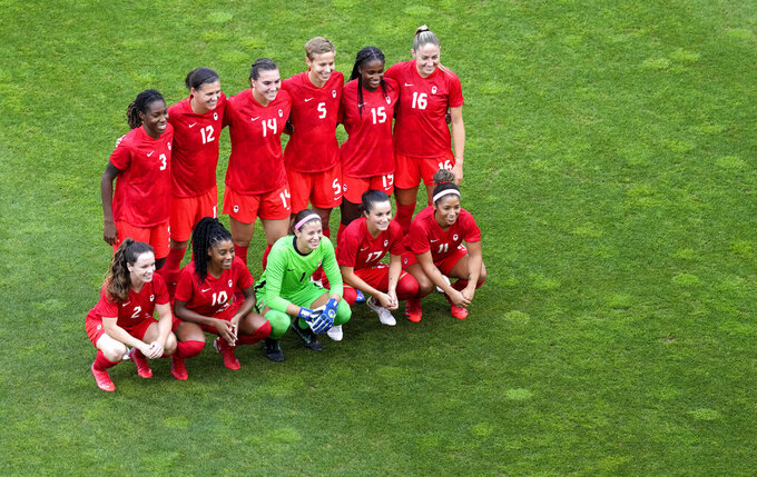 Canada's team poses for a group photo prior to a women's semifinal soccer match against United States at the 2020 Summer Olympics, Monday, Aug. 2, 2021, in Kashima, Japan. (AP Photo/Martin Mejia)