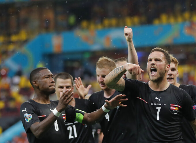 Austria's Marko Arnautovic, right, celebrates with teammates after scoring his side's third goal during the Euro 2020 soccer championship group C match between Austria and Northern Macedonia at the National Arena stadium in Bucharest, Romania, Sunday, June 13, 2021. (Robert Ghement/Poolvia AP)