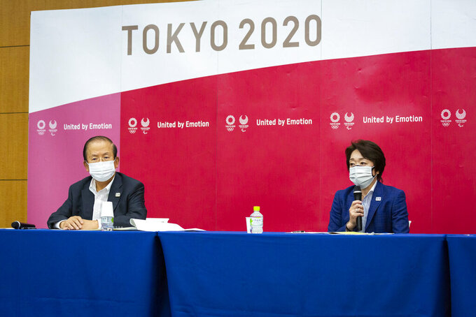 Tokyo 2020 CEO Toshiro Muto, left, and President Seiko Hashimoto attend the news conference after receiving a report from a group of infectious disease experts on Friday, June 18, 2021, in Tokyo. The experts including Shigeru Omi, head of a government coronavirus advisory panel, issued a report listing the risks of allowing the spectators and the measurements to prevent the event from triggering a coronavirus spread. (Yuichi Yamazaki/Pool Photo via AP)