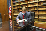 In this Tuesday, May 26, 2020 photo, U.S. Rep. Steve Watkins, R-Kan., fills out the necessary paperwork at the Kansas secretary of state's office in Topeka, Kan., to get his name on the ballot for re-election. Watkins is facing a tough primary challenge from State Treasurer Jake LaTurner. (AP Photo/John Hanna)
