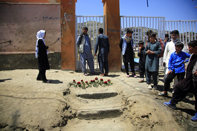 People puts flowers outside a school after a deadly attack on Saturday, in Kabul, Afghanistan, Sunday, May 9, 2021. The May 8 triple bombing of the Syed-Al-Shahada girls school that killed more than 100, nearly 80 of them Hazara students. (AP Photo/Mariam Zuhaib)