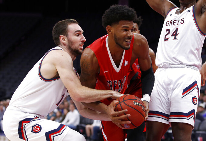 St. Mary's Tommy Kuhse, left, tries to get the ball from Fresno State forward Chris Seeley during the second half of an NCAA college basketball game in Sacramento, Calif., Wednesday, Nov. 20, 2019. Saint Mary's won 68-58. (AP Photo/Rich Pedroncelli)
