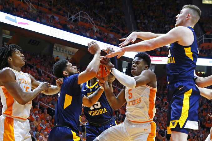 Tennessee guard Admiral Schofield (5) goes for a shot as he's defended by West Virginia guard Jermaine Haley, left, and forward Logan Routt, right in the first half of an NCAA college basketball game Saturday, Jan. 26, 2019, in Knoxville, Tenn. (AP Photo/Wade Payne)