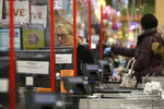 A cashier at a grocery store works while standing behind a plastic shield, Thursday, March 26, 2020, in Quincy, Mass. Grocery stores across the U.S. are installing protective plastic shields at checkouts to help keep cashiers and shoppers from infecting each other with the coronavirus. The new coronavirus causes mild or moderate symptoms for most people, but for some, especially older adults and people with existing health problems, it can cause more severe illness or death. (AP Photo/Steven Senne)