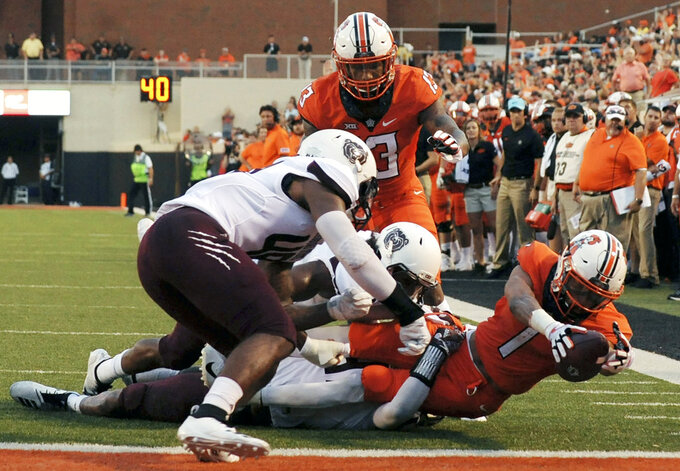 Oklahoma state wide receiver Tyron Johnson, back, watches as fellow wide receiver Jalen McCleskey, right, reaches for a touchdown while being tackled by Missouri State safety Kam Carter, left, and linebacker Tyler Lovelace, center, during the first quarter of an NCAA college football game in Stillwater, Okla., Thursday, Aug. 30, 2018. (AP Photo/Brody Schmidt)