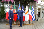 Cyprus President Nikos Anastasiadis, left, is welcomed by French President Emmanuel Macron to an emergency summit in Porticcio, Corsica island, Thursday Sept.10, 2020. Leaders of EU countries on the Mediterranean Sea are holding an emergency summit in Corsica on Thursday amid fears of open conflict with Turkey stemming from mounting tensions over oil and gas drilling. (Ludovic Marin/Pool Photo via AP)