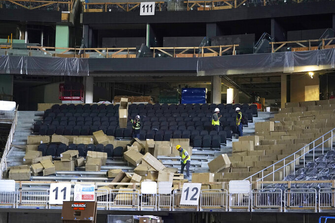 Workers install seats in a section of Climate Pledge Arena during a media tour of the facility, Monday, July 12, 2021, in Seattle. The arena will be the home of the NHL hockey team Seattle Kraken and the WNBA Seattle Storm basketball team as well as hosting concerts and other performing arts events. (AP Photo/Ted S. Warren)
