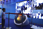 A child watches a video depicting the flow of digital information during the National Science and Technology Week exhibition held at the Military Museum in Beijing on Friday, May 24, 2019. Stepping up Beijing's propaganda offensive in the tariffs standoff with Washington, Chinese state media on Friday accused the U.S. of seeking to