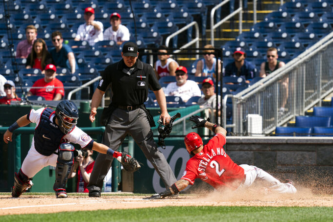 Cincinnati Reds' Nick Castellanos (2) slides home safe as Washington Nationals catcher Alex Avila, is late for a tag during the eighth inning of the resumption of a rain-delayed baseball game in Washington, Thursday, May 27, 2021. (AP Photo/Manuel Balce Ceneta)