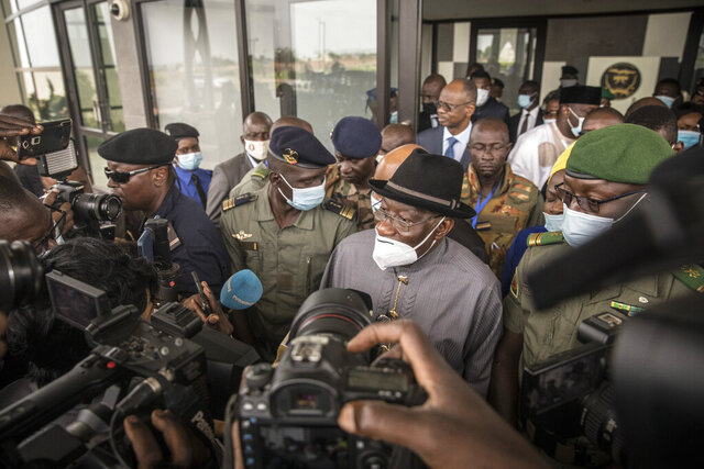 Former Nigerian president Goodluck Jonathan, center, speaks to the media after being welcomed by spokesman for the National Committee for the Salvation of the People (CNSP) Ismael Wague, center-left, and CNSP official Malick Diaw, right, upon his arrival at the airport in Bamako, Mali Saturday, Aug. 22, 2020. Top West African officials are arriving in Mali's capital following a coup in the nation this week to meet with the junta leaders and the deposed president in efforts to negotiate a return to civilian rule. (AP Photo)