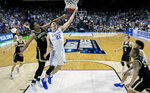 Kentucky's Reid Travis (22) goes up for a shot past Wofford's Keve Aluma, left, during the second half of a second-round game in the NCAA men's college basketball tournament in Jacksonville, Fla., Saturday, March 23, 2019. (AP Photo/Stephen B. Morton)