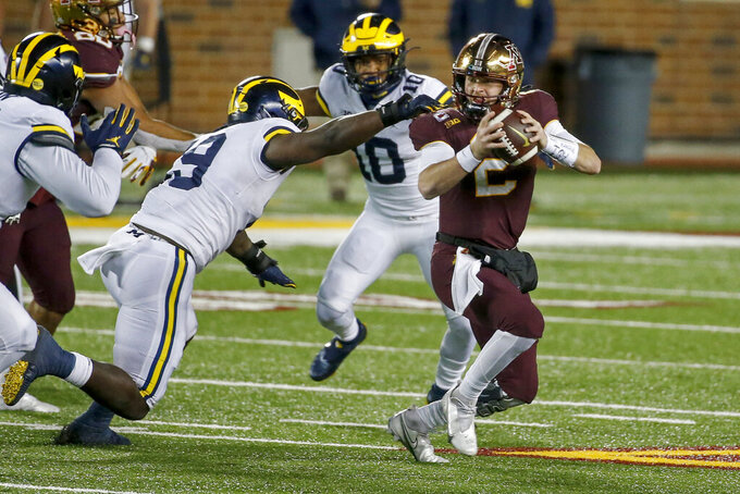 Michigan defensive lineman Kwity Paye (19) sacks Minnesota quarterback Tanner Morgan (2) in the fourth quarter of an NCAA college football game Saturday, Oct. 24, 2020, in Minneapolis. Michigan won 49-24. (AP Photo/Bruce Kluckhohn)