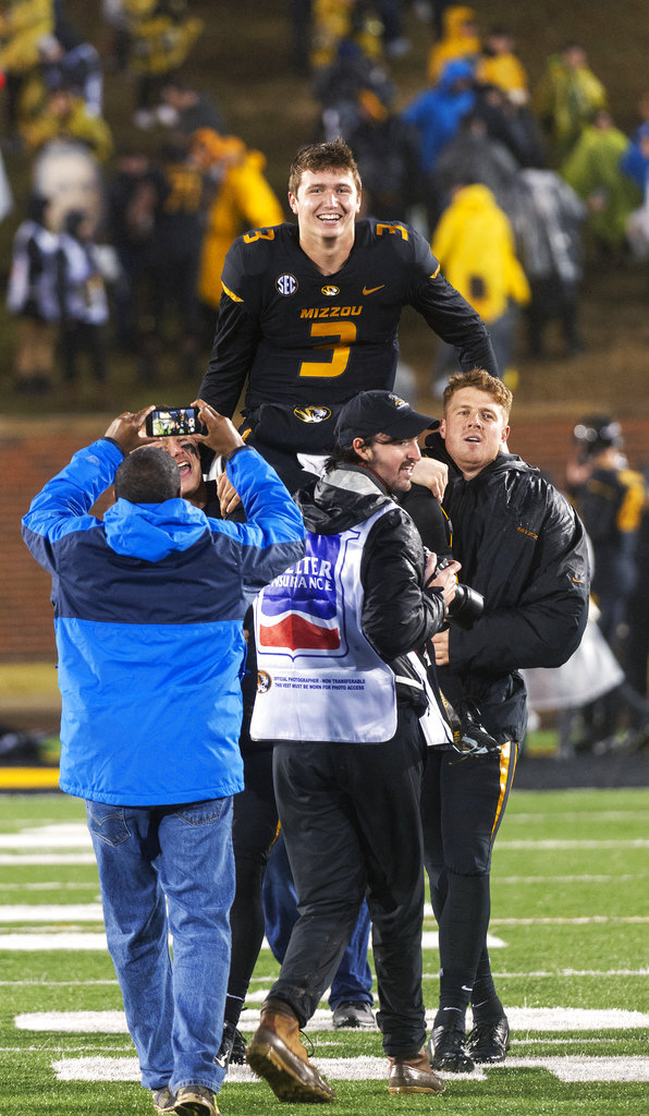 Missouri quarterback Drew Lock, top, is carried off by teammates after Missouri defeated Arkansas 38-0 in an NCAA college football game Friday, Nov. 23, 2018, in Columbia, Mo. . (AP Photo/L.G. Patterson)