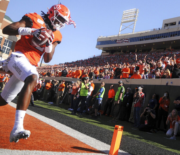 Oklahoma State wide receiver Jordan McCray scores a touchdown as fans react during the first half of an NCAA college football game against Baylor in Stillwater, Okla., Saturday, Oct. 19, 2019. (AP Photo/Brody Schmidt)