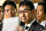 Japanese Justice Minister Katsuyuki Kawai bites his lips, surrounded by reporters, after submitting his resignation to Prime Minister Shinzo Abe at Abe's official residence in Tokyo Thursday, Oct. 31, 2019.  Kawai resigned over election fraud allegations involving his wife, also a lawmaker, and about his own gift-giving allegations reported in a tabloid magazine. (Yoshitaka Sugawara/Kyodo News via AP)