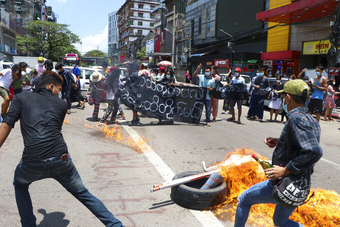 "Anti-coup protesters burn tires and chant slogans with banner read ''The Kamayut strike will be fight for to the end when we get victory"" during the demonstration against the military coup in Kamayut township Yangon, Monday, May 3, 2021. (AP Photo)"