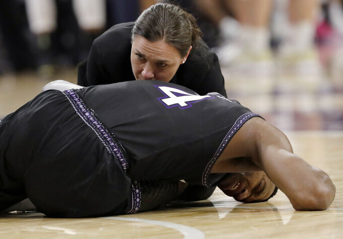 Northwestern forward Vic Law (4) is checked by after he was injured during the second half of an NCAA college basketball game against Purdue, Saturday, March 9, 2019, in Evanston, Ill. Purdue won 70-57. (AP Photo/Nam Y. Huh)