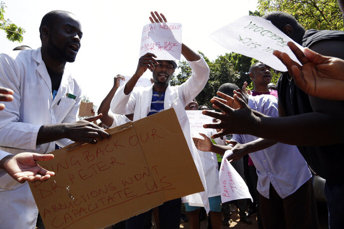 A group of Zimbabwean doctors sing as they protest at Parirenyatwa hospital in Harare, Zimbabwe, Sunday, Sept. 15, 2019. The Zimbabwe Hospital Doctors Association, which represents hundreds of junior doctors countrywide, said the association's president Peter Magombeyi was abducted on Saturday, days after receiving threats on his phone. (AP Photo/Themba Hadebe)