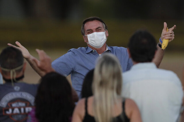 Brazil's President Jair Bolsonaro, who is infected with COVID-19, wears a protective face mask as he talks with supporters during a Brazilian flag retreat ceremony outside his official residence the Alvorada Palace, in Brasilia, Brazil, Friday, July 24, 2020. Bolsonaro has tested positive for the new coronavirus for the third time, following his July 7 announcement that he had COVID-19, the Brazilian government confirmed. (AP Photo/Eraldo Peres)