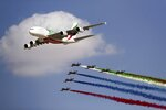 An Emirates Airline A-380 leads the