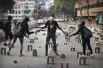 Protestors move bricks as they barricade a road near the Hong Kong Polytechnic University in Hong Kong, Thursday, Nov. 14, 2019. Hong Kong residents endured a fourth day of traffic snarls and mass transit disruptions Thursday as protesters closed some main roads and rail networks while police skirmished with militant students at major universities. (AP Photo/Kin Cheung)