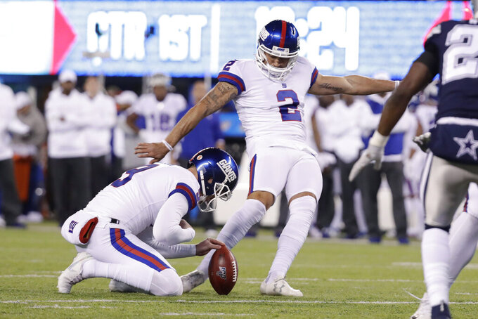 New York Giants kicker Aldrick Rosas (2) kicks a field goal with punter Riley Dixon (9) holding during the first quarter of an NFL football game against the Dallas Cowboys, Monday, Nov. 4, 2019, in East Rutherford, N.J. (AP Photo/Adam Hunger)