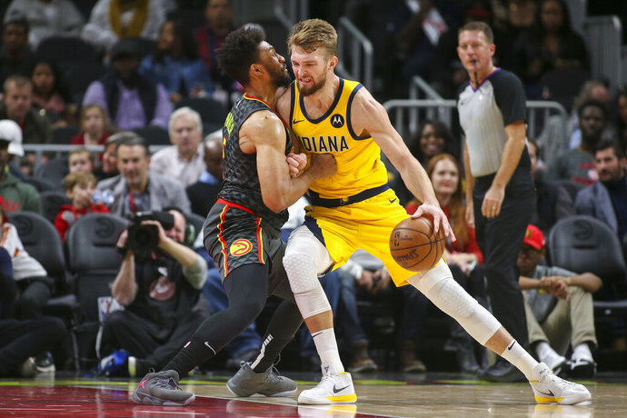 Atlanta Hawks forward Jabari Parker (5) defends against Indiana Pacers forward Domantas Sabonis, right, in the first half of an NBA basketball game Friday, Dec. 13, 2019, in Atlanta, Ga. (AP Photo/Brett Davis)