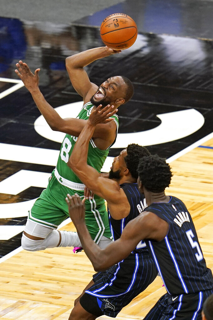 Boston Celtics guard Kemba Walker (8) goes to the basket for a shot past Orlando Magic guard Chasson Randle, center, and center Mo Bamba (5) during the first half of an NBA basketball game, Wednesday, May 5, 2021, in Orlando, Fla. (AP Photo/John Raoux)