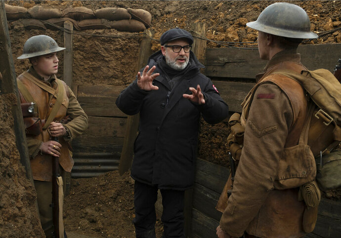 This image released by Universal Pictures shows Dean-Charles Chapman, left, director Sam Mendes, center, and George MacKay on the set of