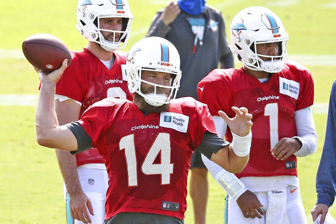 FILE - Miami Dolphins quarterback' Ryan Fitzpatrick passes as quarterbacks Tua Tagovailoa (1) and Josh Rosen (3) look on at their NFL football training facility in Davie, Fla., Monday, Aug. 17, 2020. At least four Dolphins rookies are expected to see significant action in Sunday's, Sept. 13 opener, and none of them is named Tua Tagovailoa.  (Charles Trainor Jr./Miami Herald via AP, File)