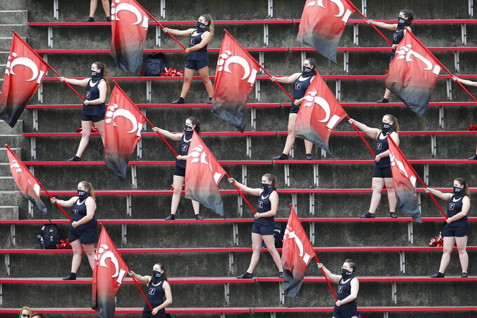 Members of the Cincinnati flag corp stay socially distanced as they perform from the stands during the first half of their NCAA college football game against Army Saturday, Sept. 26, 2020, in Cincinnati, Ohio. (AP Photo/Jay LaPrete)